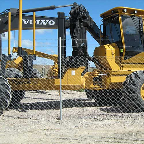 Reverse Twist Barbed Wire Security Fencing in front of front end loader